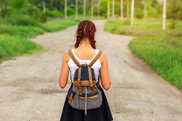 Het meisje is op de weg met een rugzak