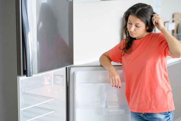 Het meisje is verbaasd over de lege koelkast. gebrek aan eten. voedsellevering.