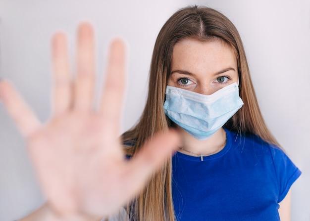 Het meisje, jonge vrouw in beschermend steriel medisch masker op haar gezicht het kijken, hand, houdt geen teken tegen. luchtverontreiniging, virus, chinees pandemisch coronavirusconcept.