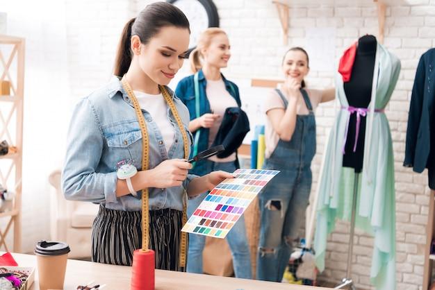 Het meisje kiest kleur in catalogus met vergrootglas