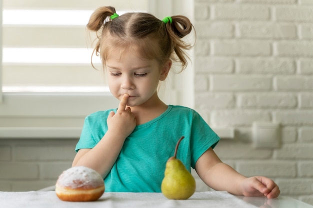 Het meisje kiest tussen doughnut en fruit.