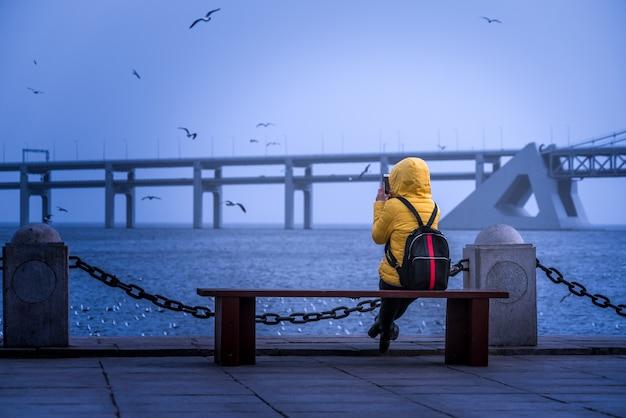 Het meisje kijkt de zee aan de zee, vroege ochtend