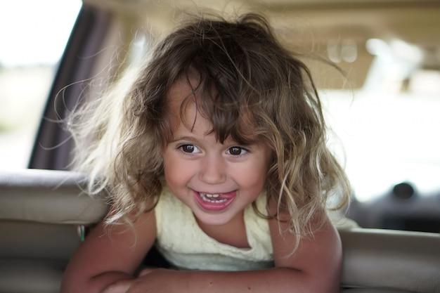 Het meisje kijkt gelukkig in de auto