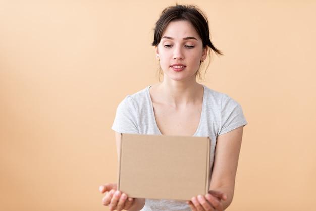 Het meisje kijkt met een glimlach en interesse naar de kartonnen doos
