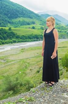Het meisje kijkt naar de bergen van georgië.