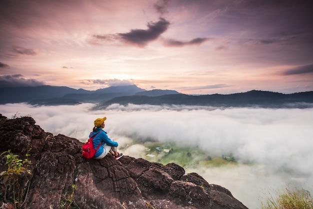 Het meisje kijkt naar de mistige zee op de hoge berg.