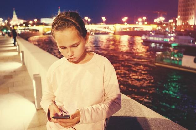 Het meisje kijkt naar de smartphone aan de waterkant op de achtergrond van avondverlichting.