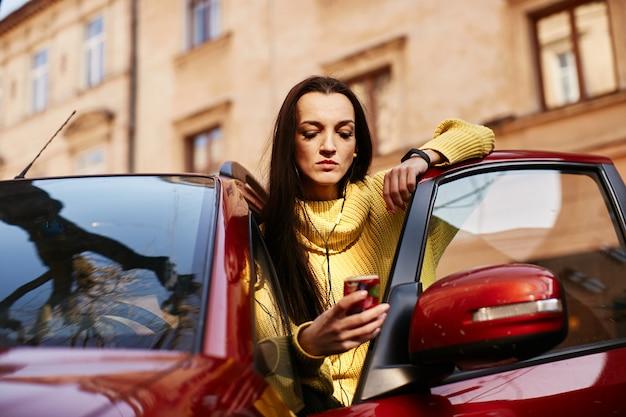 Het meisje kijkt naar de telefoon en gaat in de auto zitten