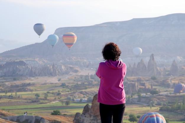 Het meisje kijkt naar de vlucht van ballonnen in cappadocië