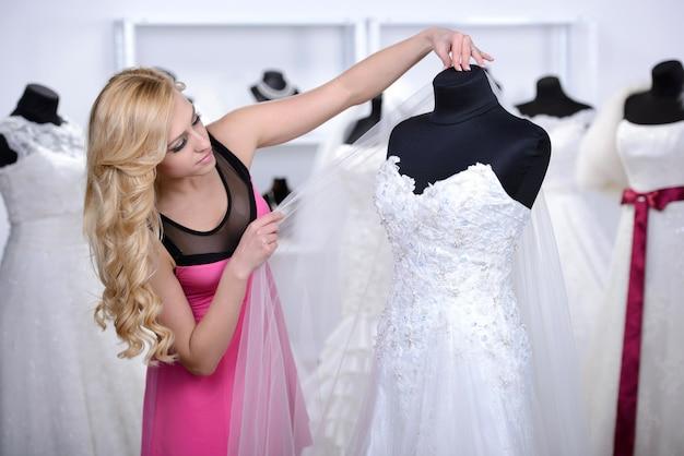 Het meisje kijkt naar de witte trouwjurk in de winkel.