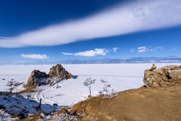 Het meisje kijkt naar kaap burhan op shamanka-rots in olkhon-eiland in zonnige maart-dag. lake baikal met prachtige wolken