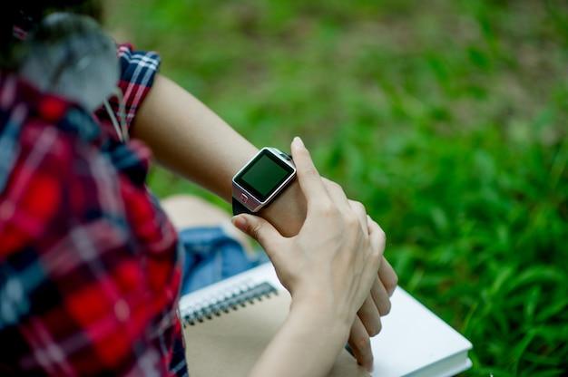 Het meisje kijkt op het horloge