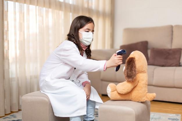 Het meisje kleedde zich als arts en medisch masker dat de temperatuur van een teddybeer met een infrarode thermometer neemt