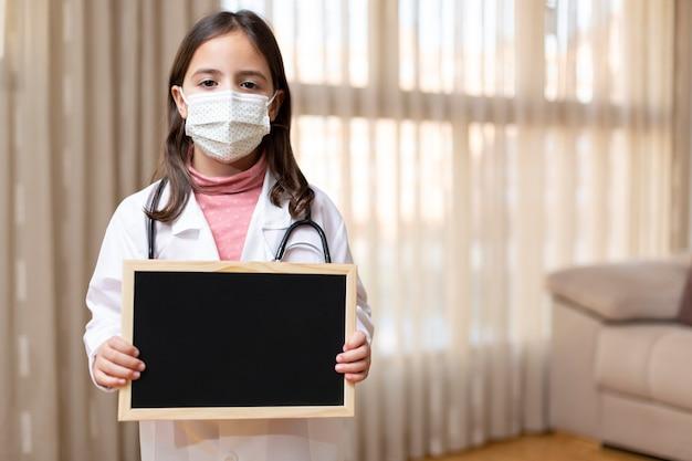Het meisje kleedde zich als arts en medisch masker dat met haar handen een schoolbord houdt