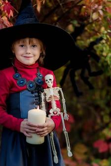 Het meisje kleedde zich als een heks die een kaars op een halloween-partij houdt.