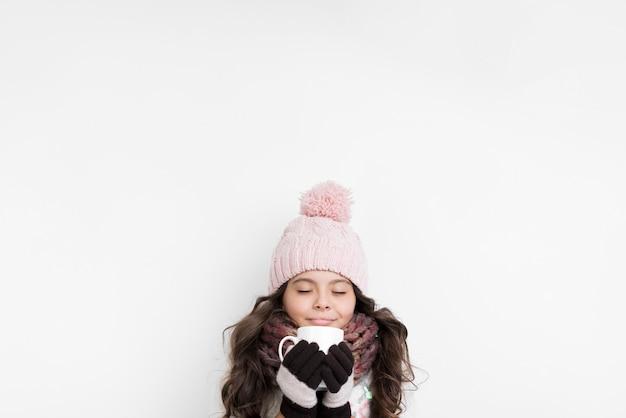 Het meisje kleedde zich warm met een kop in handen