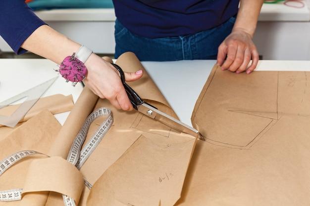 Het meisje knipt het patroon uit voor het ontwerpen van jurken en het maken van kleding