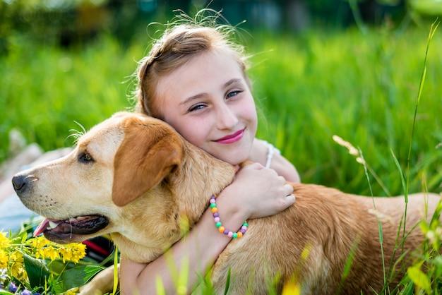 Het meisje knuffelt de hond