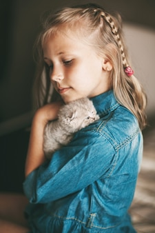 Het meisje koestert een brits klein katje