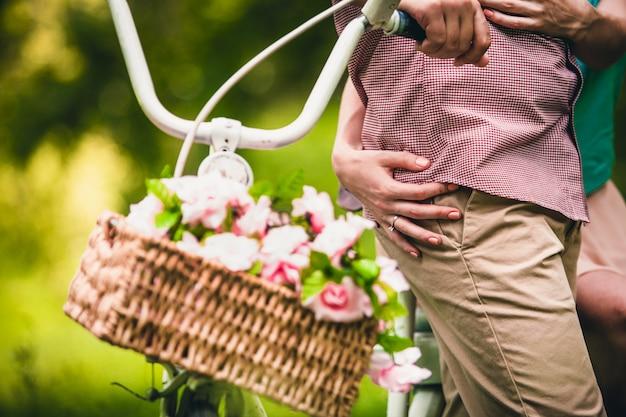 Het meisje koestert een man in geruit overhemd dichtbij een fiets met een mand van rozen in het park