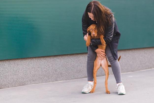 Het meisje koestert een mooie bruine hond