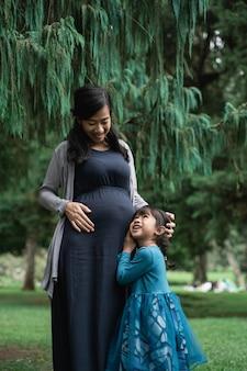 Het meisje koestert haar zwangere moeder
