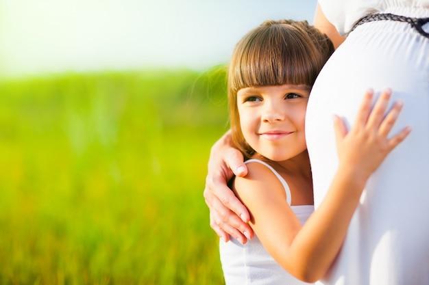 Het meisje koestert mamma zwangere buik
