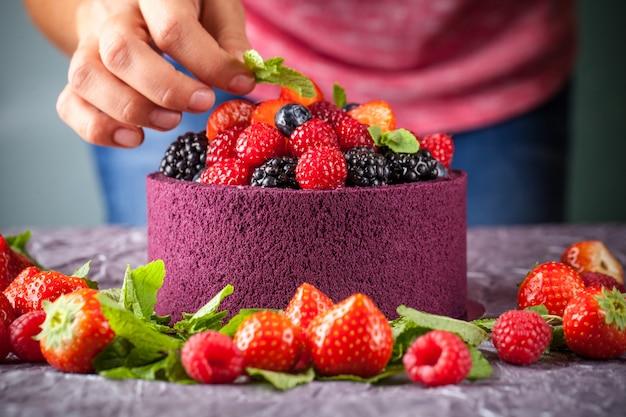 Het meisje kookt een cake die met bessen, aardbeien, frambozen en munt wordt verfraaid