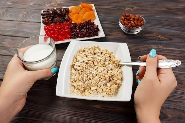 Het meisje kookte haar muesli als ontbijt. het meisje eet havermoutpap dat zou afvallen en een dieet zou volgen. handig en gezond ontbijt. donker houten, bovenaanzicht