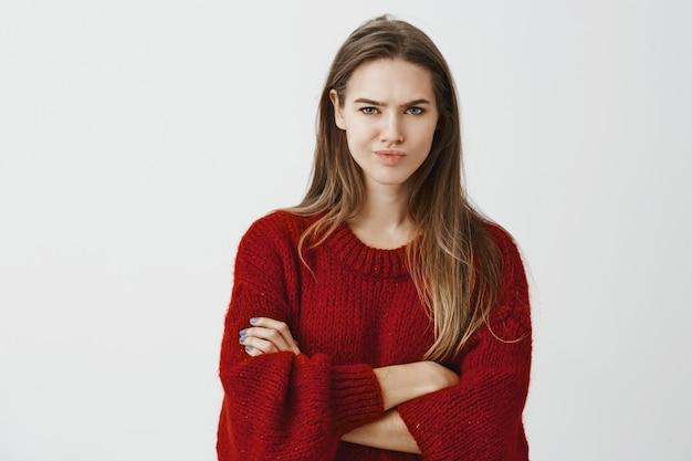 Het meisje koopt geen domme verklaringen. portret van twijfelachtige ontevreden creatieve baas in rode losse trui, hand in hand gekruist op de borst en fronsend van grijns, uiting van ongeloof en aarzeling