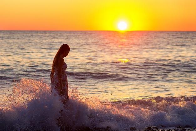 Het meisje kost in golven aan de zee bij zonsondergang