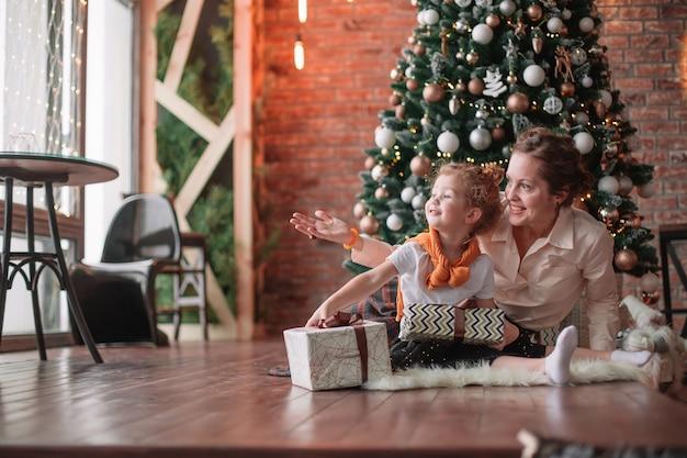 Het meisje kust haar moeder dichtbij de kerstboom