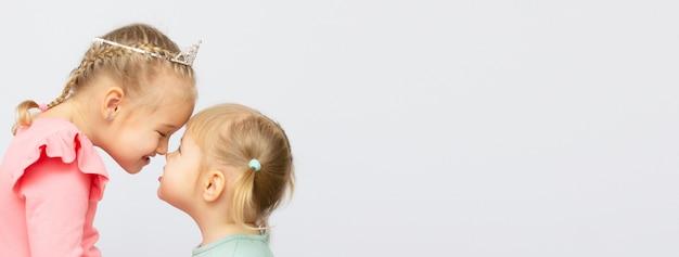 Het meisje kust haar zus op een witte achtergrond met kopie ruimte banner