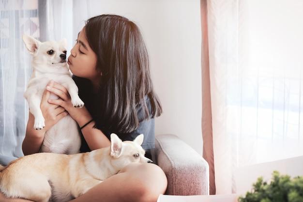 Het meisje kuste de hond en een andere hond lag op haar schoot.