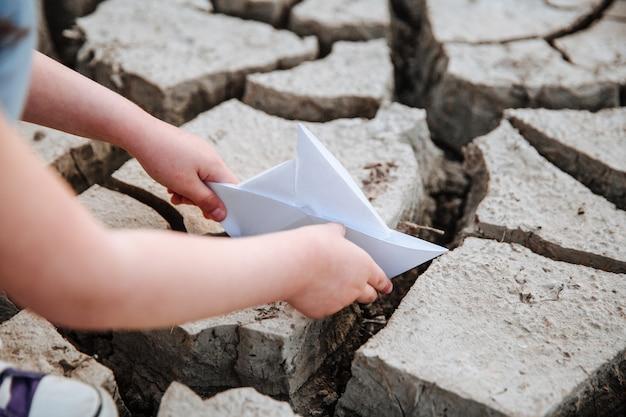 Het meisje laat de papieren boot op de droge, gebarsten grond zakken watercrisis en klimaatveranderingsconcept