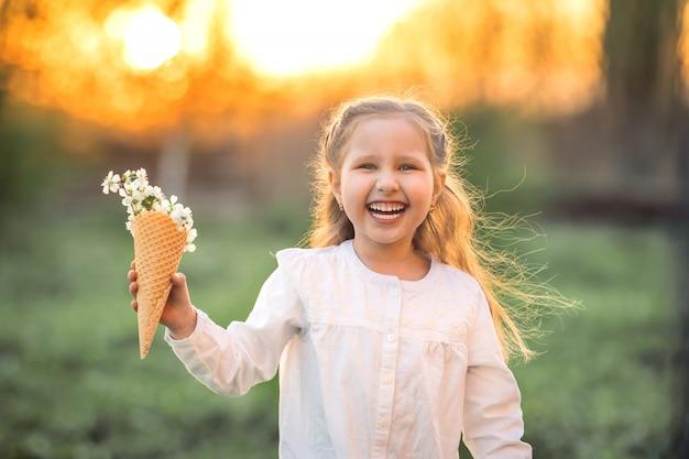 Het meisje lacht en houdt de lentebloemen van de boom in wafelkegel in hand