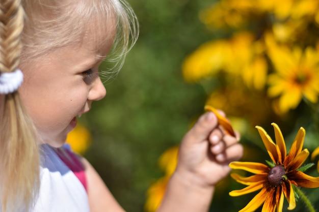 Het meisje lacht en scheurt een bloemblaadje af van een gele madeliefjebloem