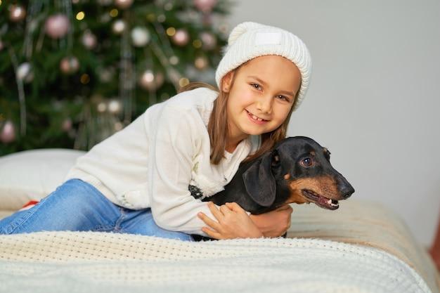 Het meisje lacht met haar vriend een teckelhond dichtbij de kerstboom