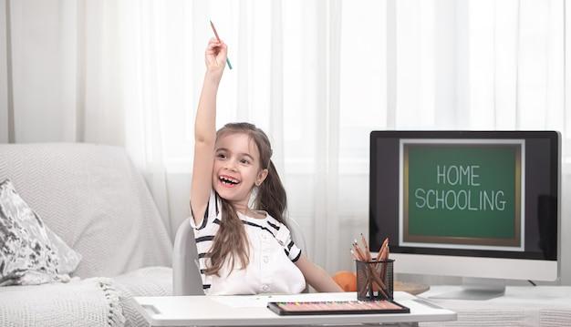 Het meisje lacht thuis studeren. thuisonderwijs concept.