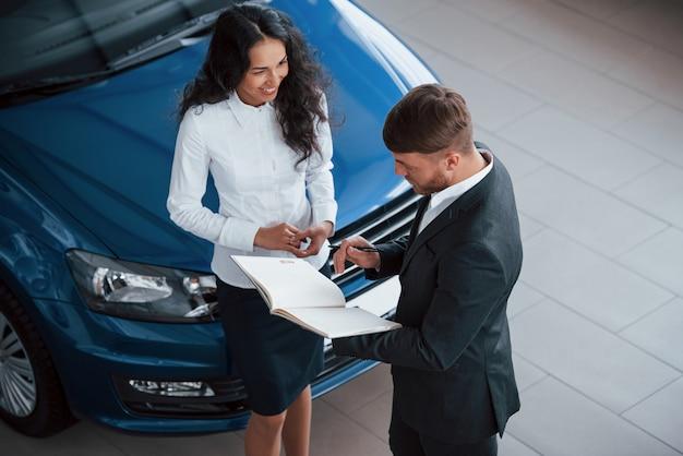 Het meisje lacht. vrouwelijke klant en moderne stijlvolle bebaarde zakenman in de auto-salon