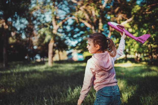 Het meisje lanceert een speelgoedvliegtuig in de lucht in het park