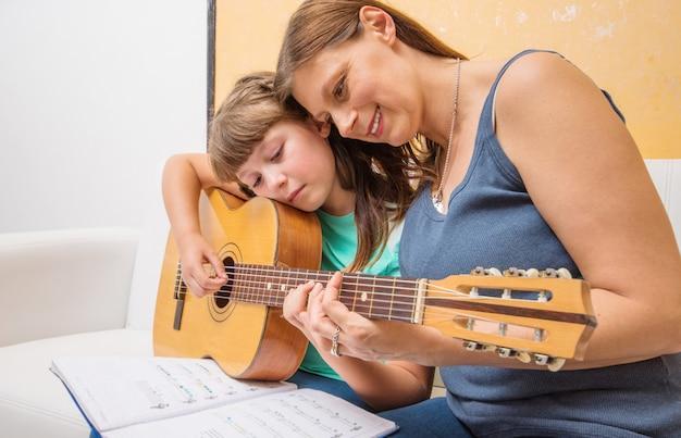 Het meisje leert om gitaar te spelen met steun van zijn moeder thuis