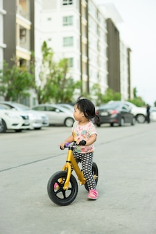 Het meisje leert om in evenwicht te brengen fiets op de weg