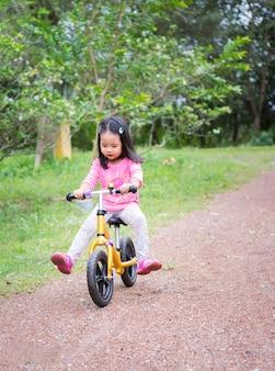 Het meisje leert om in evenwicht te brengen fiets op helling in het park