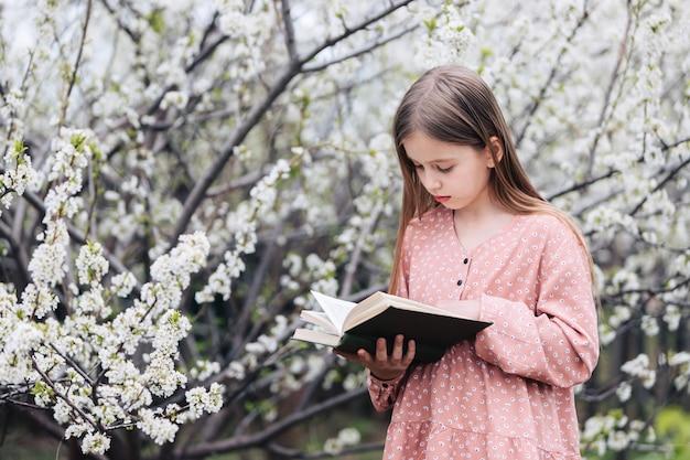 Het meisje leest een boek dichtbij een bloeiende boom in de tuin.