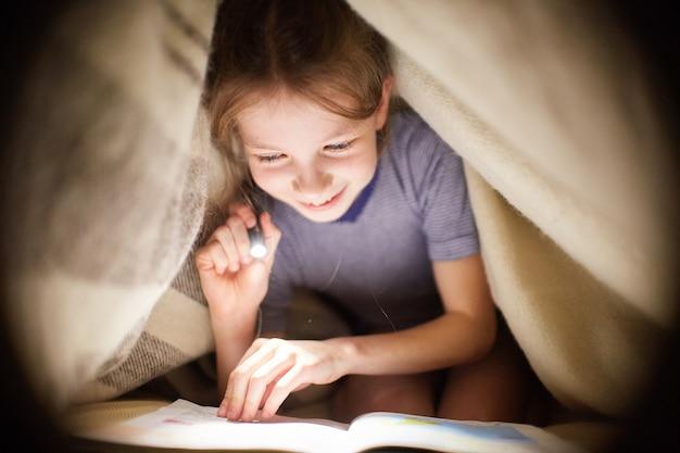 Het meisje leest een boek onder een deken met een flitslicht in een donkere ruimte bij nacht