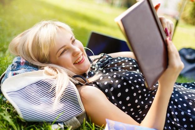 Het meisje leest een boek op het grasveld met ochtendzon.