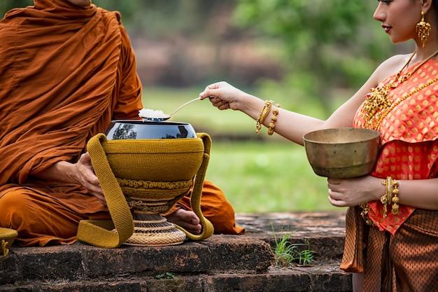 Het meisje legde rijst aan de priester.