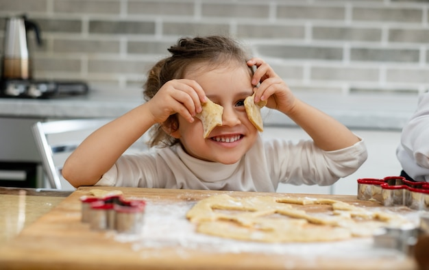 Het meisje legt de losse stukjes deeg voor hun ogen