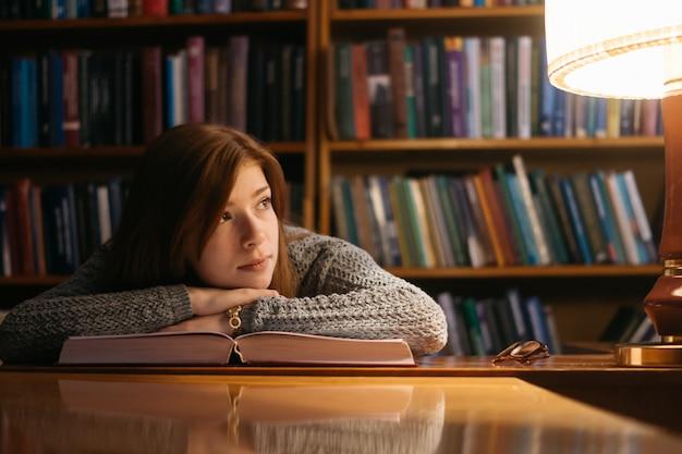 Het meisje leunde op het boek. het meisje in de bibliotheek